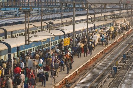 delhi: New Delhi, India - February 5, 2009: People crowd a platform alongside a train at New Delhi railway station in Delhi, India. Editorial