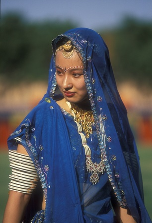 sari: Jodhpur, India - el 6 de octubre de 2006: Retrato de una hermosa dama vestida con un sari azul se recorta con lentejuelas, joyer�a y pulseras. Imagen es de un concursante en la mejor competici�n de vestido de mujer en el Festival de Jodhpur en Jodhpur, Rajasthan, India.