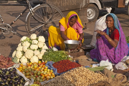 Jaipur, India - November 12, 2007: Indian women in brightly colored saris selling fruit and vegetables by the side of the road in Jaipur, Rajasthan, India.