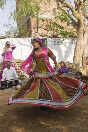 Jaipur, India - March 9, 2009: Beautiful tribal dancer in colorful costume performing in Jaipur, Rajasthan, India