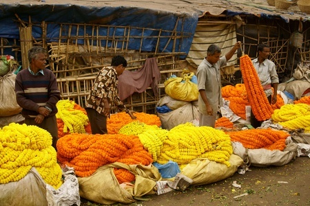 Calcutta, India - December 18, 2008: People selling flowers at the flower market in the shadow of the Haora Bridge in Kolkata, West Bengal, India