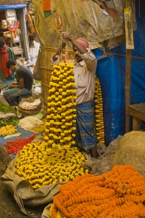Calcutta, India - December 19, 2008: Man selling floral garlands in the flower market in Calcutta, West Bengal, India.