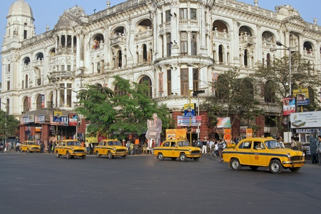 kolkata: Calcutta, India - December 18, 2008: Yellow taxis crossing a busy road junction in Calcutta West Bengal India.