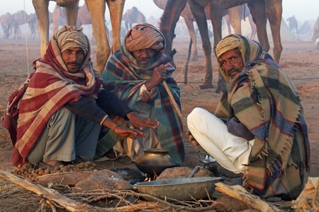 clustered: Nagaur, Rajasthan, India - February 15, 2008: Indian men wrapped in blankets clustered around an open fire at the Nagaur Cattle Fair, Rajasthan, India Editorial