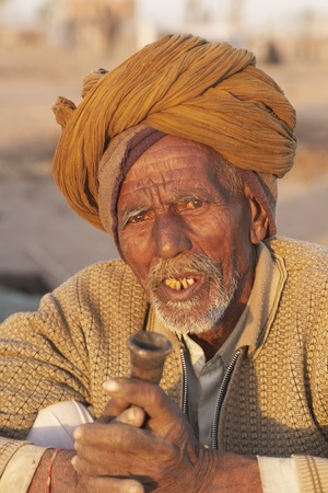 Nagaur, Rajasthan, India - February 15, 2008: Old Indian man in a turban smoking a pipe at the Nagaur Cattle Fair in Rajasthan, India