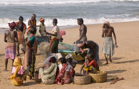 Puri, Orissa, India - May 14, 2008: Fishing boat on a sandy beach in Orissa, India. Fishermen removing the catch from the nets. Women sitting on the ground waiting to take the fish to market.
