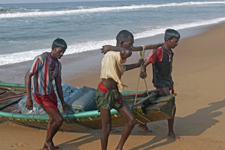 boat lift: Puri, Orissa, India - May 14, 2008: Fishermen carrying their boat ashore after a night out at sea fishing. Puri, Orissa, India