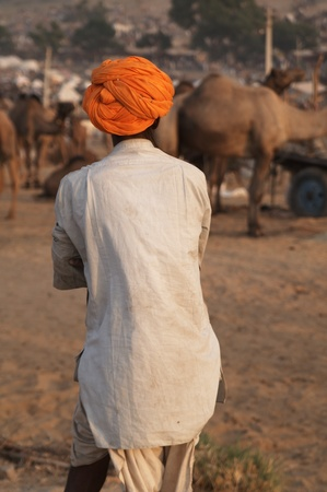 dhoti: Pushkar, Rajasthan, India - November 19, 2007: Man in orange turban and white dhoti at Pushkar Camel Fair Rajasthan India Editorial