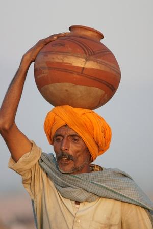 turban: Pushkar, Rajasthan, India -  November 9, 2008: Indian man in orange turban carrying pot of water on his head at the Pushkar Fair, Rajasthan, India Editorial