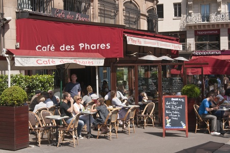 Paris, France - July 26, 2009: Street cafe filled with people in Paris, France