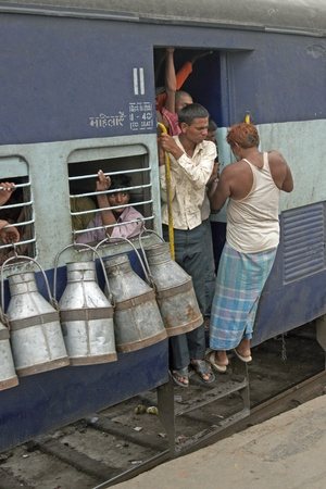 Delhi, India -  July 18, 2008 :Men hanging onto the doorway of a moving train. Milk churns hanging from the window in Delhi, India.