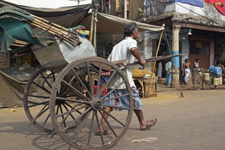 calcutta: Calcutta, India - December 17, 2008: Man pulling a traditional hand pulled rickshaw along a street in Calcutta West Bengal India.  Editorial