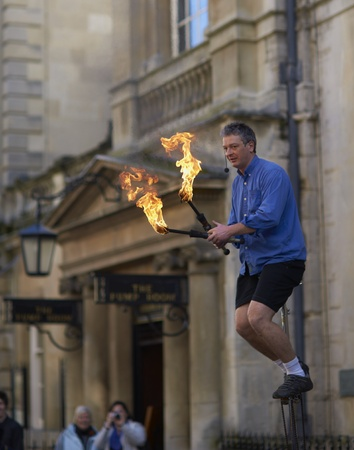 Bath, England - February 26, 2011: Street artist entertaining the crowds by juggling flaming torches whilst riding a unicycle in Bath, Somerset, England.