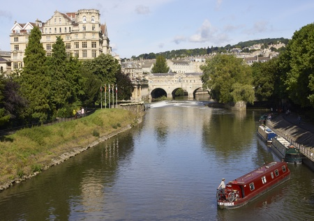 Bath, England - August 28, 2010: Man navigating a narrow boat along the River Avon in Bath, Somerset, England.