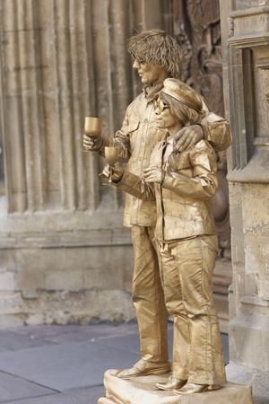 Bath, England - August 28, 2010: Street artists posing as statues dressed in golden costume seeking money from tourists in Bath, Somerset, England. Stock Photo - 11940894