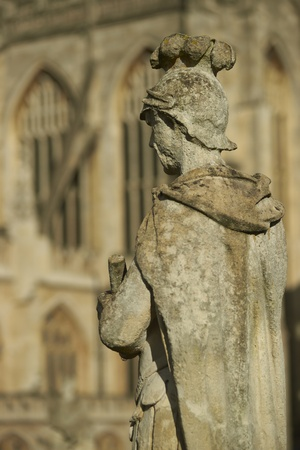 Old weathered stone statue above the ancient Roman Baths in Bath, Somerset, England  Bath Abbey in the background  photo