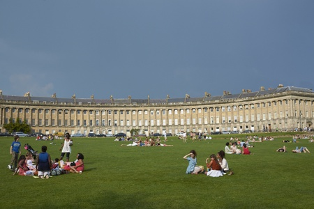 Bath, England - April 23, 2011: Groups of people enjoying the sunshine on the grass in front of the Royal Crescent in Bath, Somerset, England. Stock Photo - 13266321