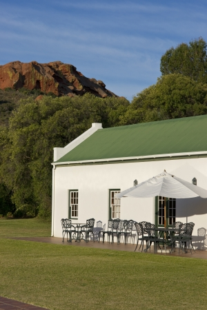 Oudtshoorn, South Africa - September 3, 2011: Farm cottage built in traditional Cape architectural style set in landscaped grounds in the Oudtshoorn region of the Western Cape in South Africa