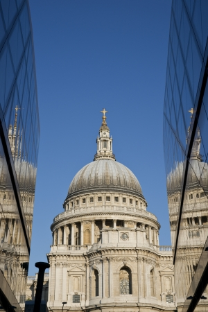 St Pauls Cathedral reflected in the glass walls of a modern building in London, England photo