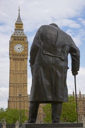 Statue of Winston Churchill in Parliament Square in London, England with the Elizabeth Tower of the Houses of Parliament in the background photo