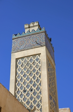 Minaret decorated with a mozaic of blue tiles and patterned stonework at the historic Madrasa Bou Inania in the ancient medina of Fes in Morocco photo