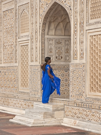 Agra, India - October 2, 2008: India woman in blue salwar kameez entering the doorway into the ornate white marble Mughal tomb (I Stock Photo - 18329177