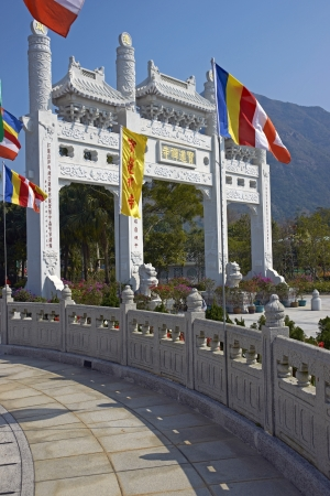 Ornate white stone gateway adorned with colorful flags at the Po Lin Buddhist monastery located on Ngong Ping Plateau on Lantau Island, Hong Kong, China photo