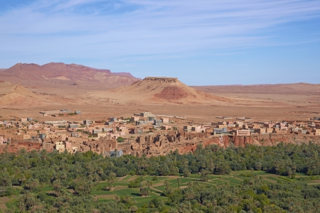 mud house: Traditional Berber village and cultivated fields along a river valley in the foothills of the Atlas Mountains in Morocco