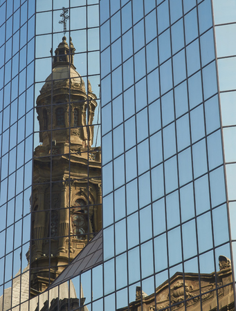 catholic church: Tower of the historic Catedral Metropolitana reflected in the glass of a modern office building in the Plaza de Armas in Santiago, Chile