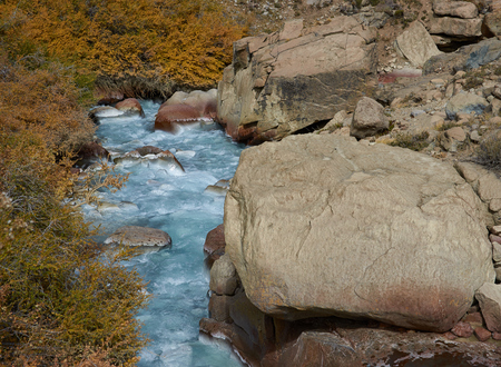 Ice cold river from the Paloma glacier running through autumn coloured vegetation in the Yerba Loca Mountain Park near Santiago in Chile photo