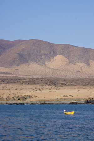 inshore: Small inshore fishing boat in the bay at the small fishing village of Carrizal Bajo off the coast of the Atacama Desert in Chile Stock Photo