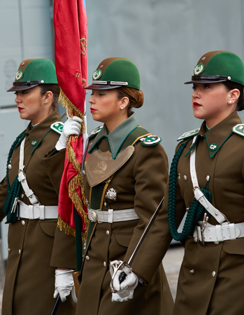 paramilitary: Santiago, Chile - August 4, 2014  Female members of the Carabineros marching with a ceremonial flag as part of the changing of the guard ceremony at La Moneda in Santiago, Chile