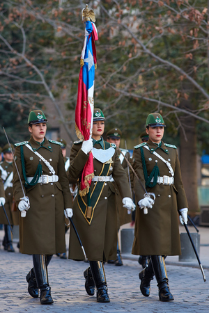 paramilitary: Santiago, Chile - August 8, 2014  Members of the Carabineros marching with a ceremonial flag as part of the changing of the guard ceremony at La Moneda in Santiago, Chile