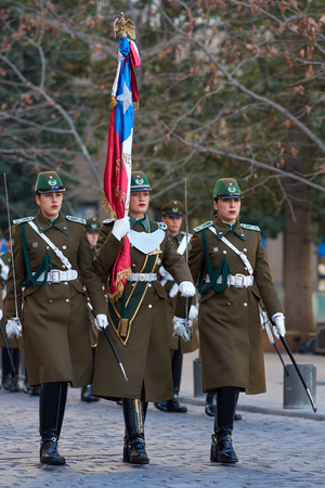 Santiago, Chile - August 8, 2014  Members of the Carabineros marching with a ceremonial flag as part of the changing of the guard ceremony at La Moneda in Santiago, Chile                                                      Editorial