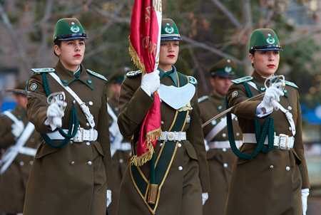 Santiago, Chile - August 8, 2014  Members of the Carabineros marching with a ceremonial flag as part of the changing of the guard ceremony at La Moneda in Santiago, Chile