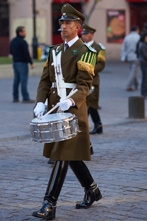 paramilitary: Santiago, Chile - August 8, 2014  Member of the Carabineros Band marching and playing the drum as part of the changing of the guard ceremony at La Moneda in Santiago, Chile