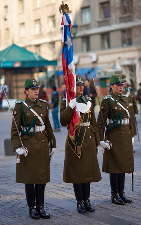 paramilitary: Santiago, Chile - August 12, 2014  Members of the Carabineros marching with a ceremonial flag as part of the changing of the guard ceremony at La Moneda in Santiago, Chile Editorial