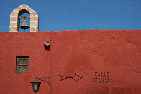 Bell tower perched above the red painted walls of the historic Monasterio de Santa Catalina in Arequipa, Peru photo