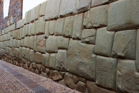 former years: Stone wall from a former Inca Palace in Cusco, Peru containing a large and famous twelve sided stone carved by Inca craftsmen over 500 years ago.