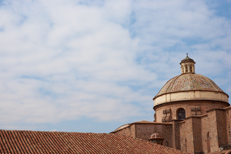 Colourfully tiled dome of the historic Iglesia de la Compania seen across the red rooftops of Cusco in Peru. The church dates back to 1571 and sits on top of an old Inca Palace. Stock Photo