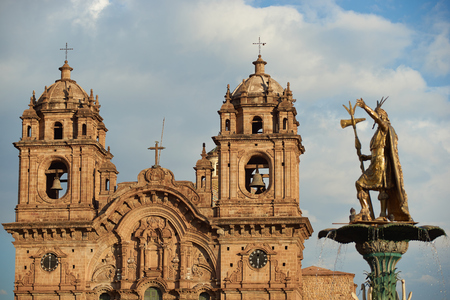 Golden statue of an Inca on top of the fountain in the centre of the Plaza de Armas in Cusco, Peru. In the background is the historic Iglesia de la Compania, which dates back to 1571 and sits on top of an old Inca Palace.