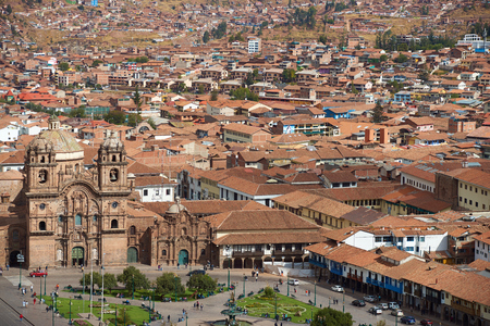 The historic Plaza de Armas in the historic former Inca capital of Cusco in Peru. The Iglesia de la Compania is the prominent red stone building with twin towers and a colourfully tiled dome forming part of the roof.