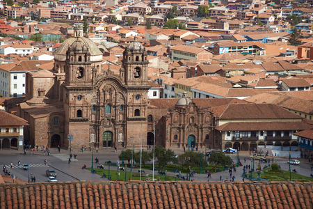 iglesia de la compania: The historic Plaza de Armas in the historic former Inca capital of Cusco in Peru. The Iglesia de la Compania is the prominent red stone building with twin towers and a colourfully tiled dome forming part of the roof.