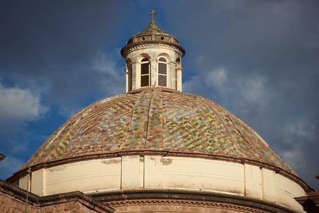 Colourfully tiled dome of the Iglesia de la Compania in the Plaza de Armas of Cusco in Peru. The dome is illuminated against dark storm clouds.