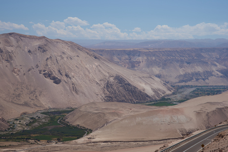irrigated: Irrigated green fields in the bottom of the Rio Lluta valley in the dry desert of northern Chile. The main road from Arica to Bolivia runs along part of the valley.