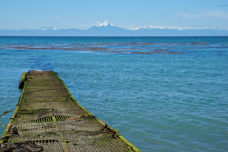 Jetty jutting out into the sea from the Island of Chiloe towards the snow capped mountains and the Corcovado Volcano on the mainland of Chile. photo