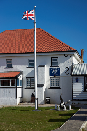 falkland: Royal Falkland Islands Police Headquarters in Stanley, capital of the Falkland Islands. White painted building with red corrugated iron roof.
