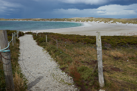 yorke: Gravel walkway leading to the curved sandy beach of Yorke Bay in the Falkland Islands. The bay is home to a breeding colony of Magellanic Penguins (Spheniscus magellanicus) and is close to the Stanley, capital of the Falkland Islands. Stock Photo