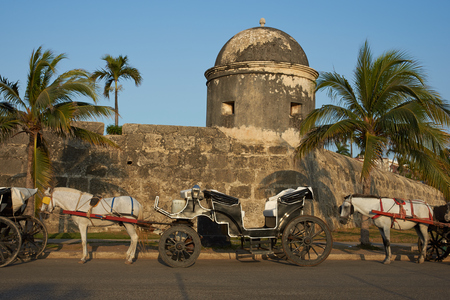 fortified: Horse drawn carriages used by tourists waiting alongside the fortified walls of the historic Spanish colonial city of Cartagena de Indias in Colombia
