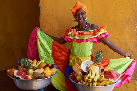 28: Cartagena de Indias, Colombia - January 28, 2015: Woman in traditional costume selling fruit in the historic walled city of Cartagena de Indias in Colombia